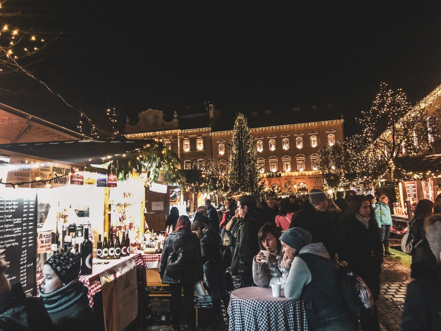 crowd of people gathered inside the square at obuda christmas market