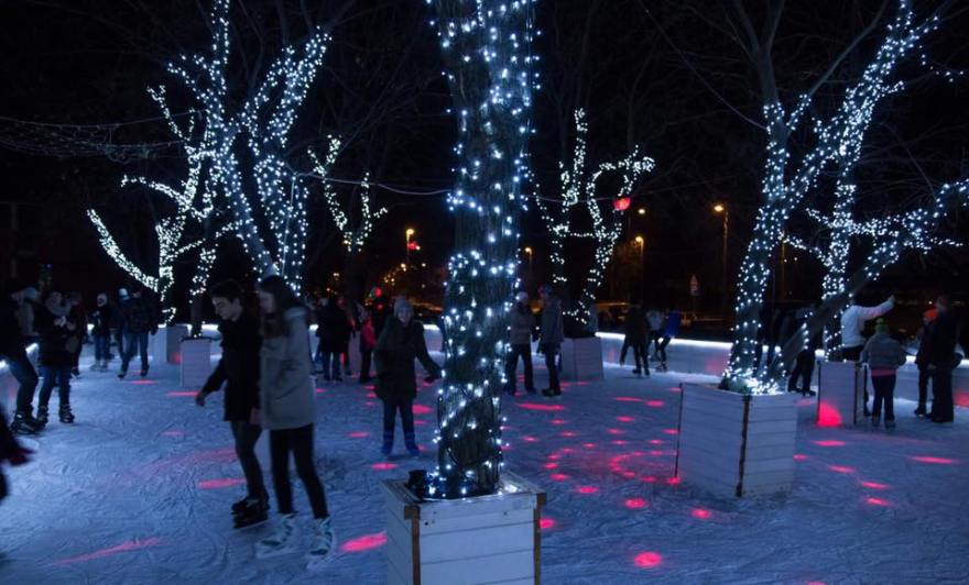 people-skating-at-night-on-outdoor-ice-rink-with-fairy-lit-trees