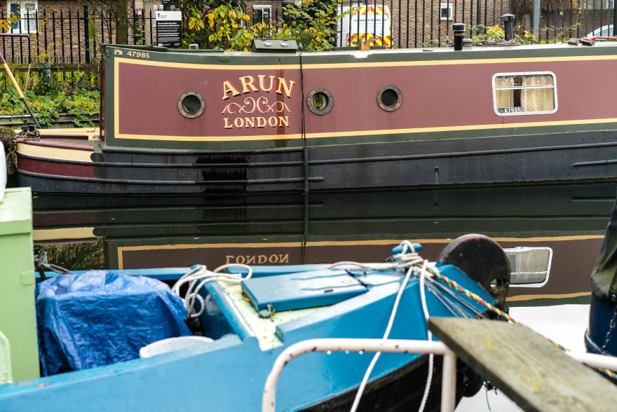 blue houseboat docked with white rope in front of a yellow green and black narrowboat that reads