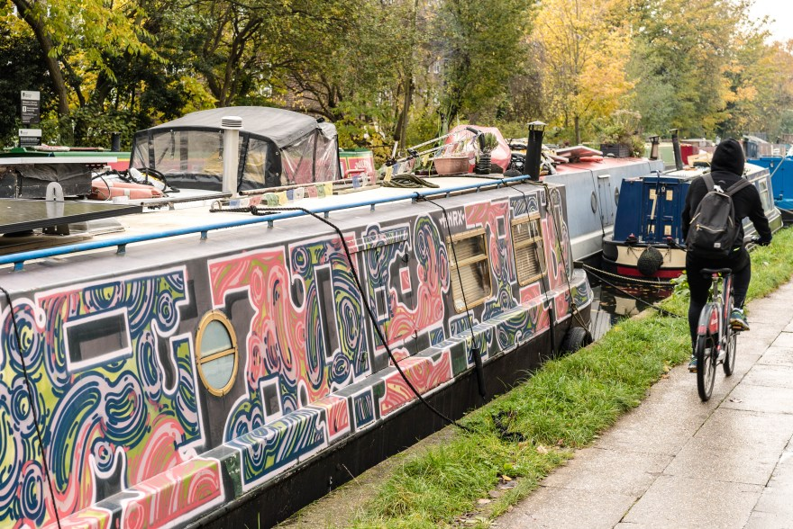 a man with a backpack riding a read bike next to a houseboat that is covered in pink, green and blue graffiti