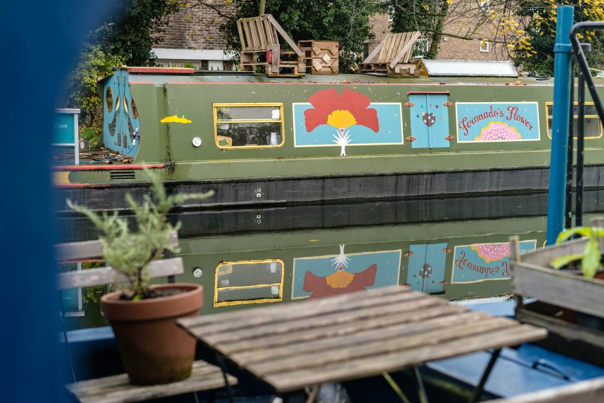 plantpot and wooden chairs in front of a green boat that has a yellow red flower and a blue and pink sign the that says