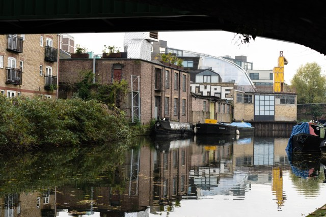 canal with water that is reflecting the surroundings next to brown buildings and street art that reads