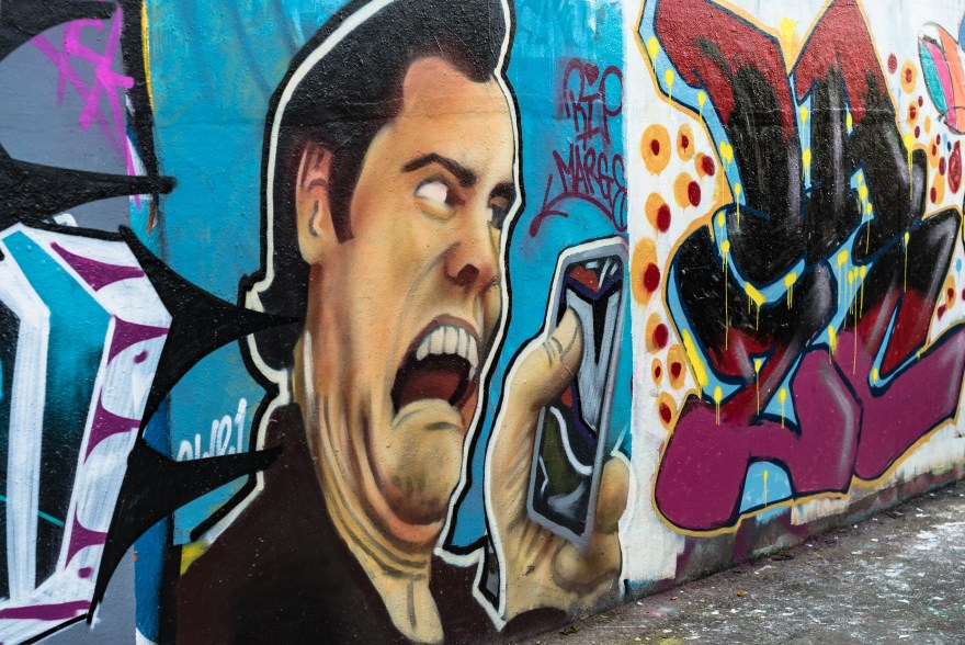 street art in brick lane showing jim carey with his mouth open looking worried whilst staring at the phone in his hand
