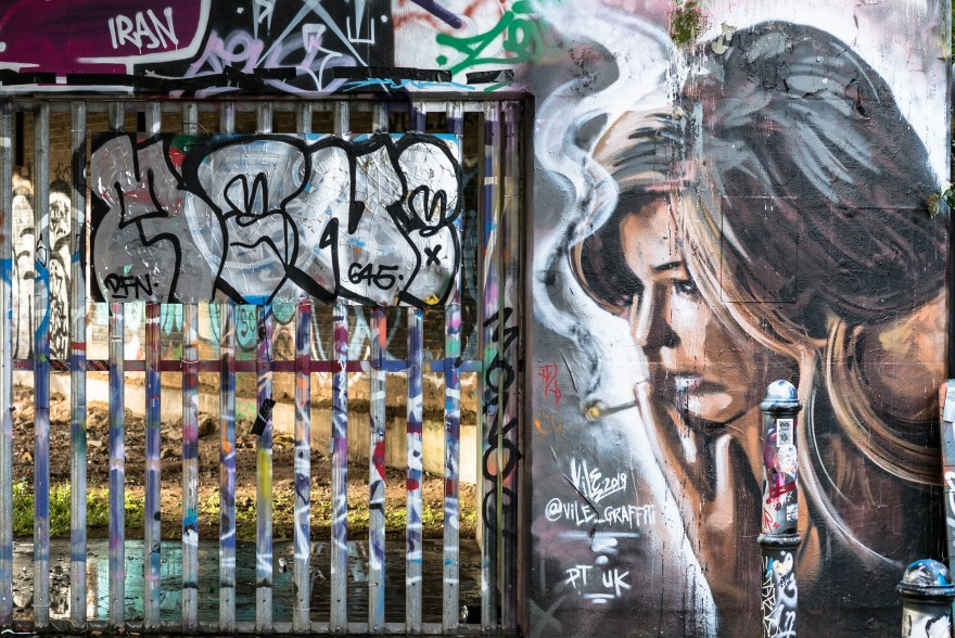 street art in brick lane showing a white women with brown blond hair smoking
