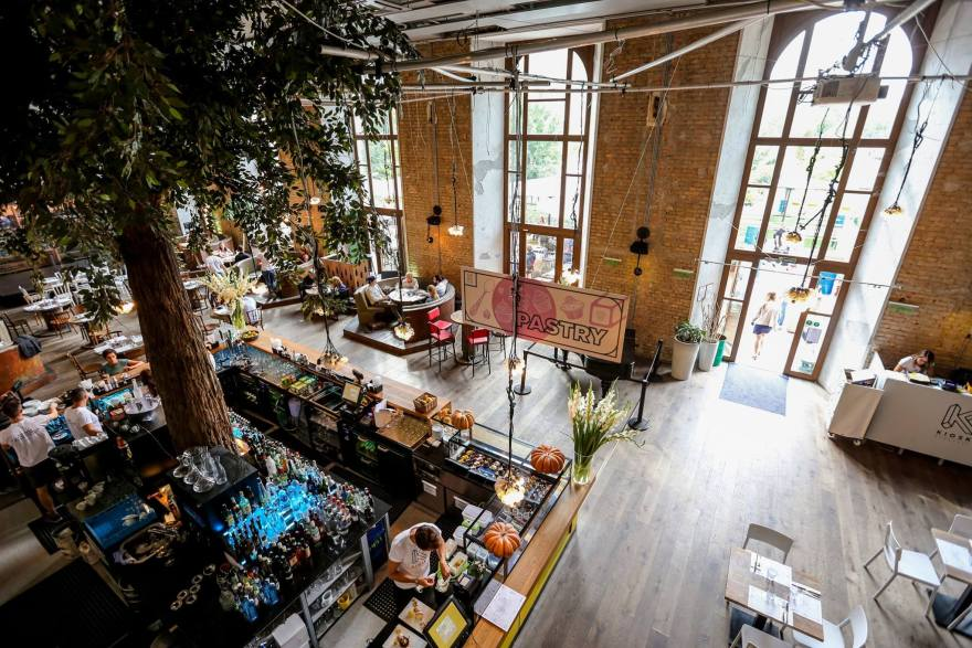 """bare bricked will restaurant in budapest that has tall tree in the middle of the bar and a pink and white sign that says """"pastry"""""""
