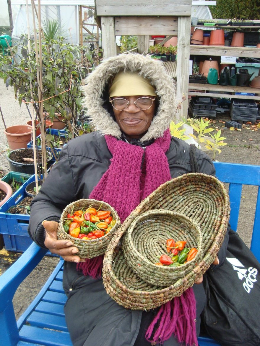 black women with a hat holding thatched basket of green yellow orange chillies