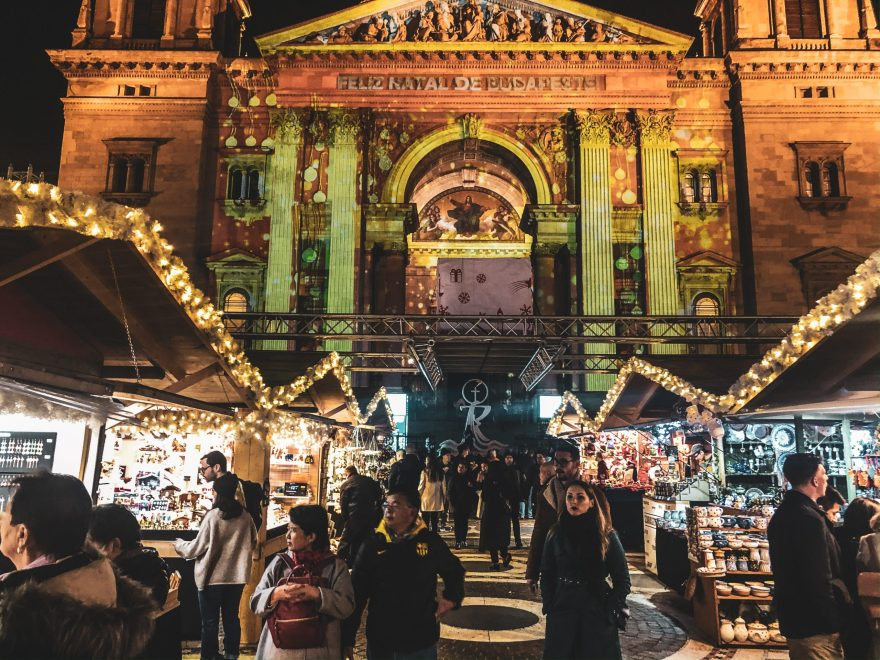 people browsing stalls that line the walkway in front of the 3D lit St Stephen's Basilica Christmas market