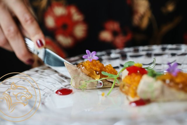 women with red nail varnish cutting through orange caviar covered with flowers on a white and black plate