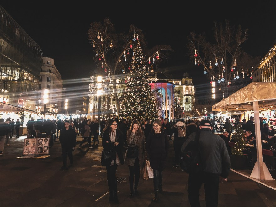 people walking in front of a decorated christmas tree at Vörösmarty Square christmas market