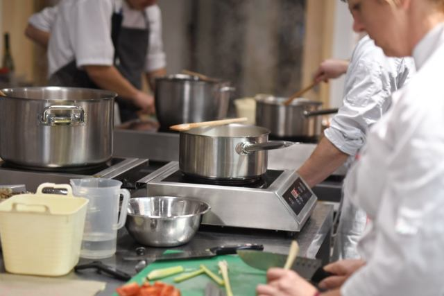 chefs wearing white overalls cooking in steel silver pan s on electric hobs