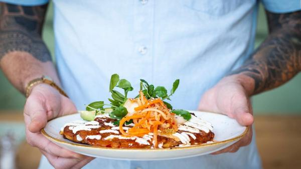 man in blue shirt with a tattoo sleve holding a plate with a kimchi pancake topped off with carrot slices coriander and lime