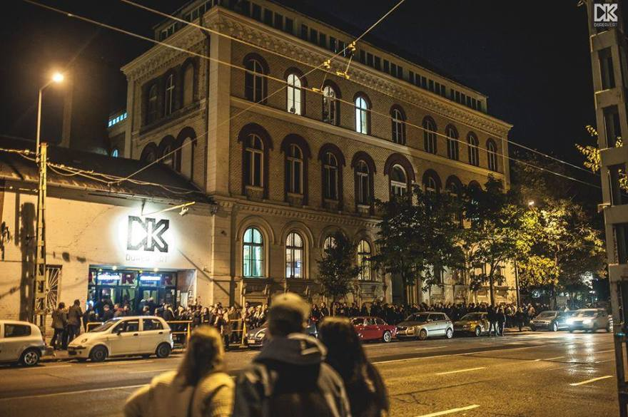 big queue outside a ruin bar in budapest that has a black logo which says DK