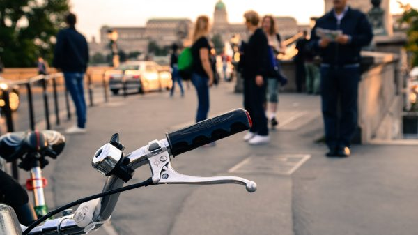 image of a a bike on the szechenyi chain bridge with a blurred view of buda castle in the distance