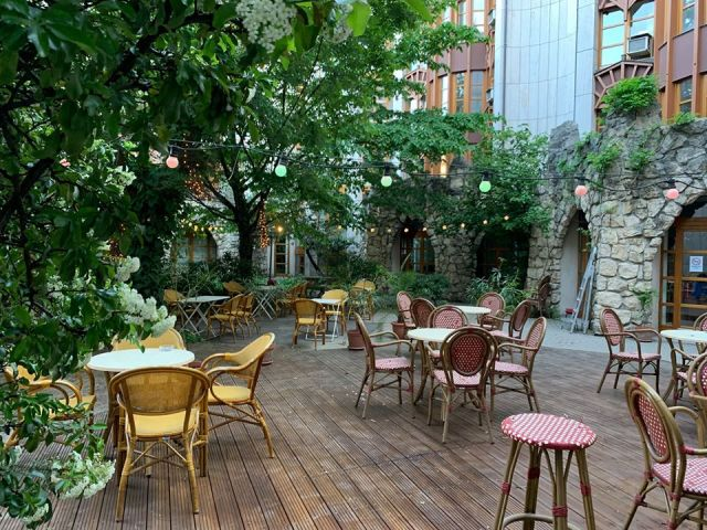 Bereg Budapest wooden floored outdoot terrace lones with wooden furniture green plants and trees