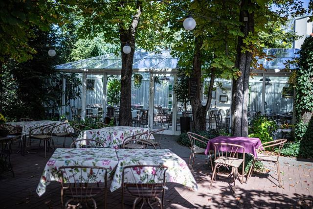 an outdoor terrace surrounded by trees with metal chairs and tables covered in flowery purple table clothes jardinette budapest