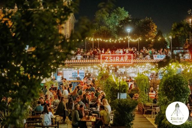 Zsiráf Budapest outdoor bar packed full of people to a backdrop of bright light signs and greenery where people are sitting and talking.