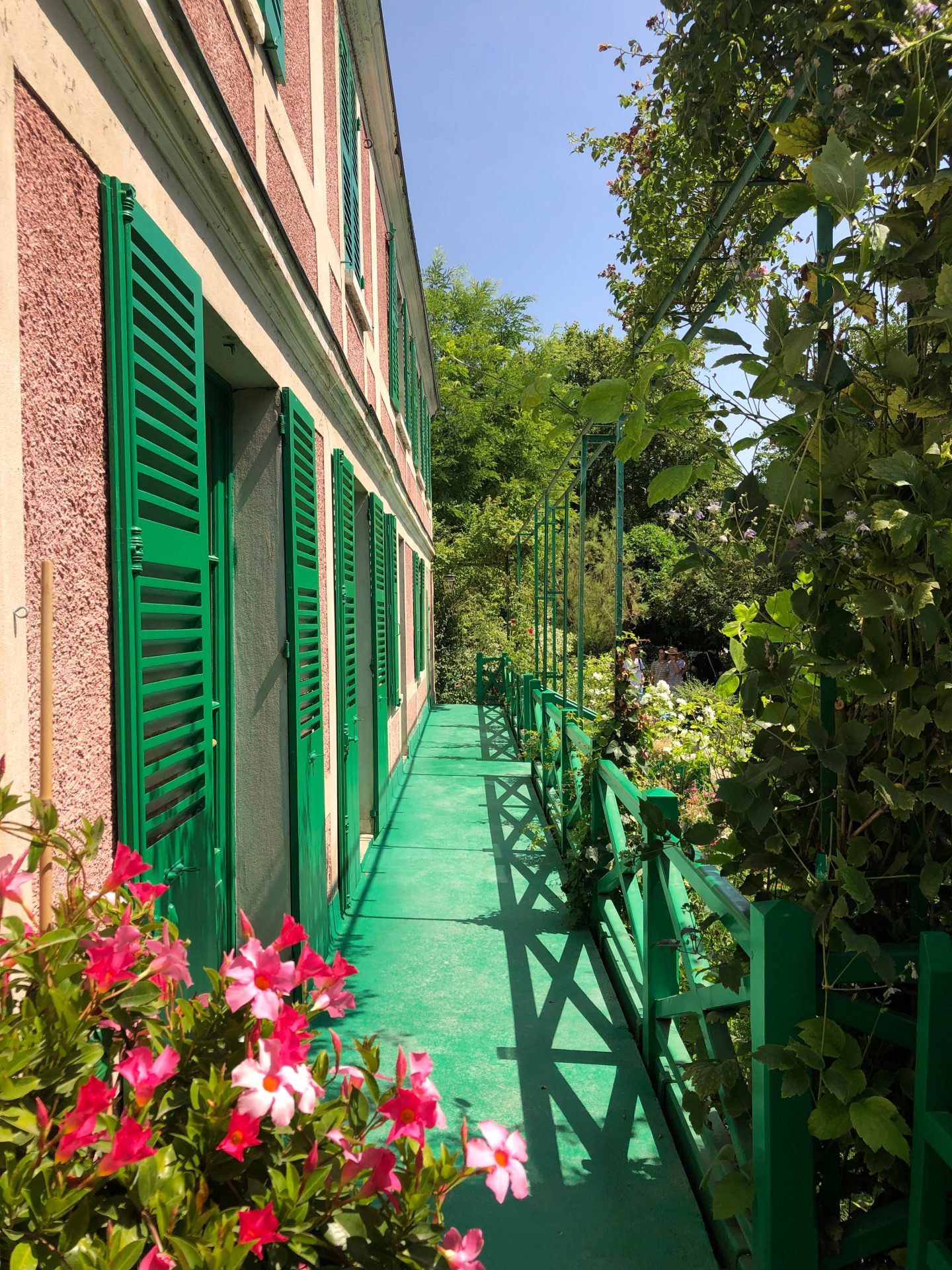 The Veranda of Monet's pink house with green shutters