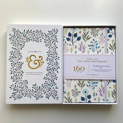 Archer and Olive white dot grid notebook with a beautiful floral cover in a white box.