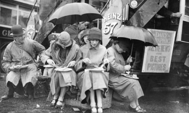Epsom racegoers having lunch under umbrellas in the rain 1925