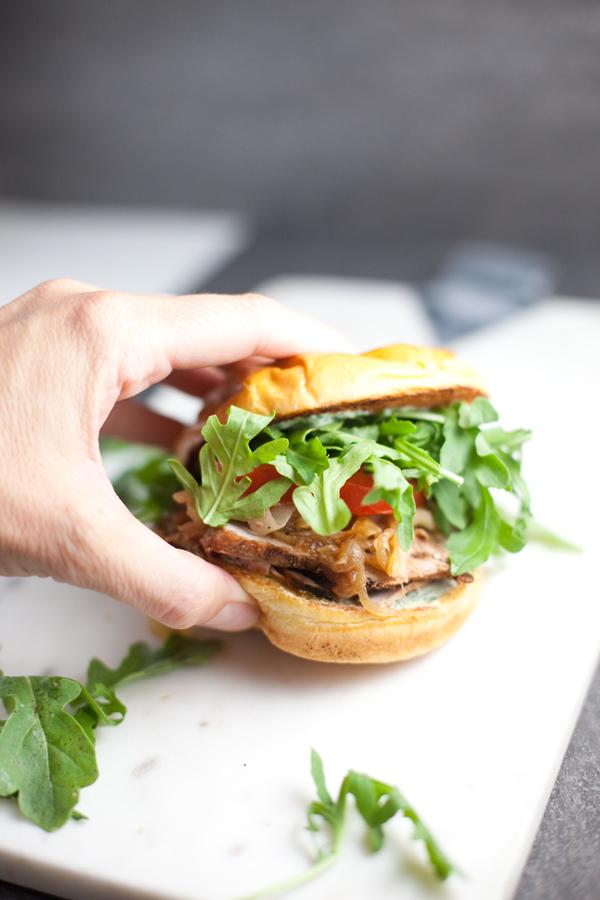 Pork Tenderloin Sandwich with lots of arugula being held