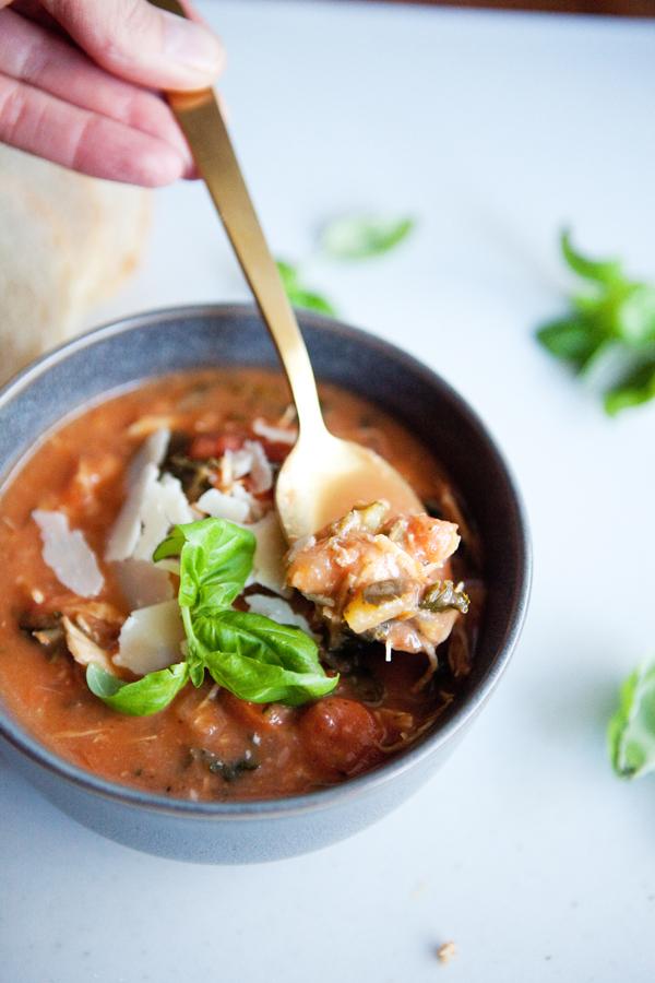 A bite of Creamy Tomato Chicken Soup in a bowl
