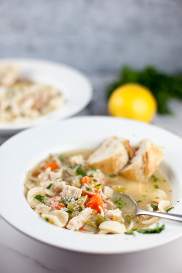 Two bowls of chicken soup with bread
