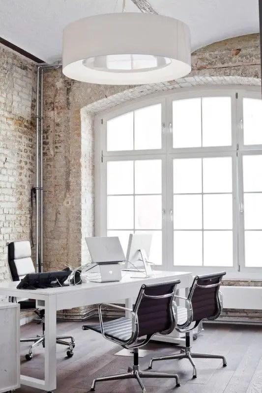 Le modernisme du bureau est contrebalancé par le mur derrière lui