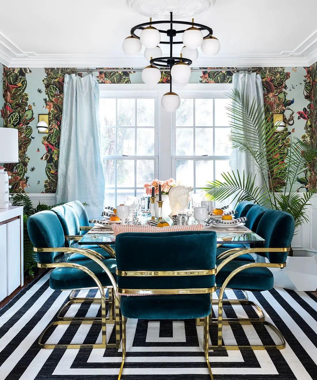 Cette belle salle à manger est décoré d'un papier peint bleu en motif tropique avec une table en verre. Les chaises bleus en velours donne une touche de calme sur un tapis noir et blanc.