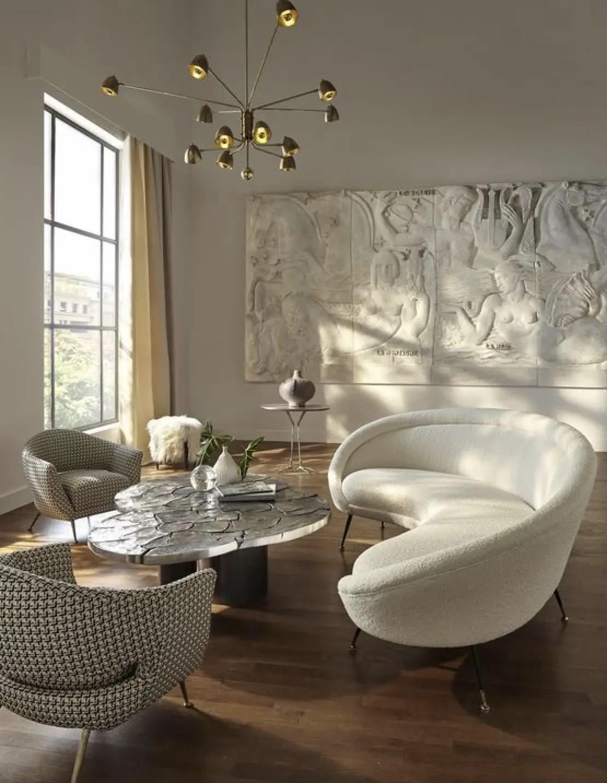 Un salon qui sert comme un bel exemple de cette tendance 2020, aménagé d'un canapé, des chaises et une table basse courbés.