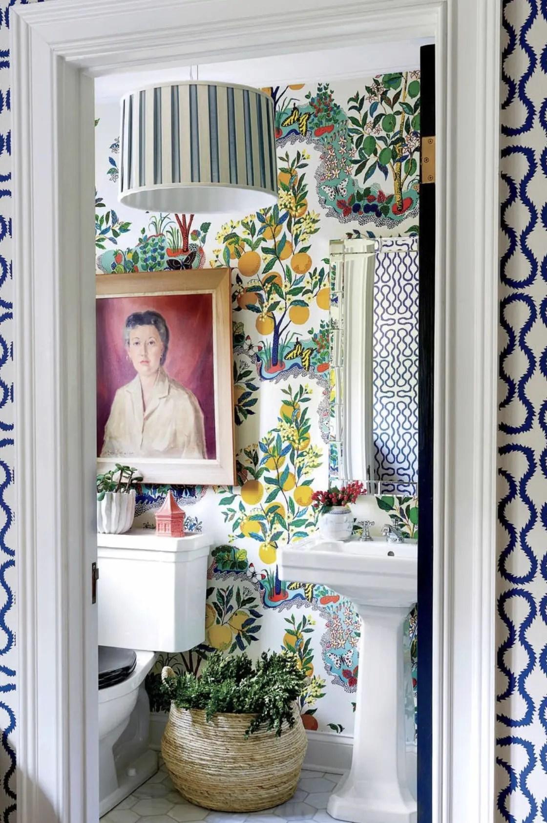 Cette salle de toilette nous offre de la fraîcheur avec un papier peint des citronniers.