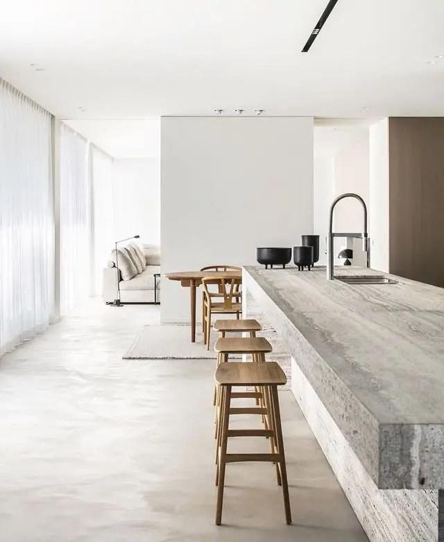 Cuisine ouverte sur le salon avec couleurs neutres et mobilier épuré.