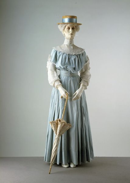 Day Dress, c. 1905, British; Crisp-looking blue and white dresses such as this were popular for boating and seaside wear. This dress was worn by Miss Heather Firbank (1888-1954), daughter of the affluent Member of Parliament Sir Thomas Firbank and sister of the novelist Ronald Firbank. Summer day dress consisting of a bodice, skirt and two belts. Flared skirt composed of four 28-inch widths of printed blue and white striped cotton pleated onto the narrow waistband. The bodice is pouched at the front and slightly bloused at the back. The circular yoke consists of tucked Broderie Anglaise frills and a pin-tucked cotton infill, and with a high-boned (using five bones) pin- tucked collar finished with a tape lace frill. Sleeves with short flared striped over sleeves which are gathered into the armholes bordered with Broderie Anglaise and frills. The inner plain white cotton sleeves are narrow, tucked and reach the elbow. The bodice is lined with white cotton, and fastened with original hooks, eyes and loops. Pearl buttons. Pleated belts with five bones and hook and eye fastenings concealed by a rosette. Machine stitched. There is evidence of minor alterations. Victoria & Albert Museum (T.21 to C-1960)
