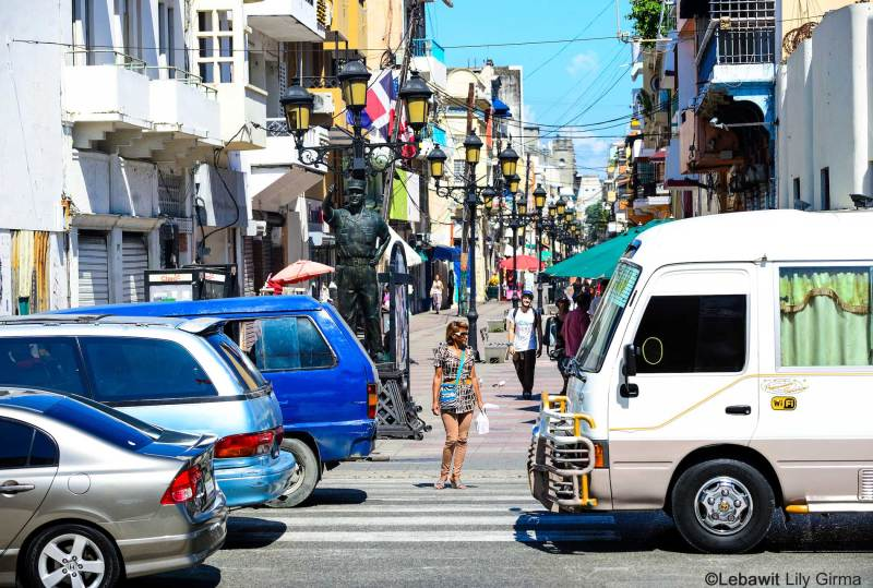 A woman stopped at a crosswalk in Santo Domingo with traffic passing by.