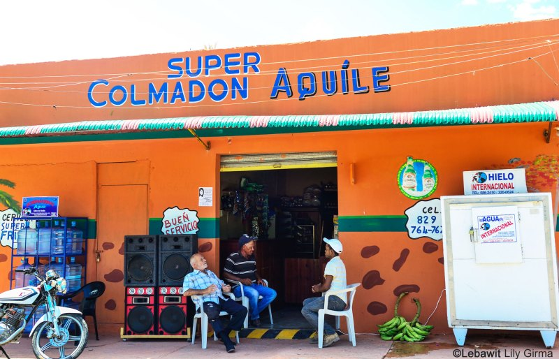 Three men sitting and chatting outside a local store or colmado in the Dominican Republic.