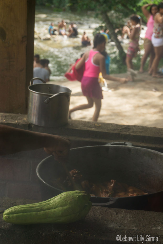 Food cooking in pt and children playing by river in Manabao, Dominican Republic