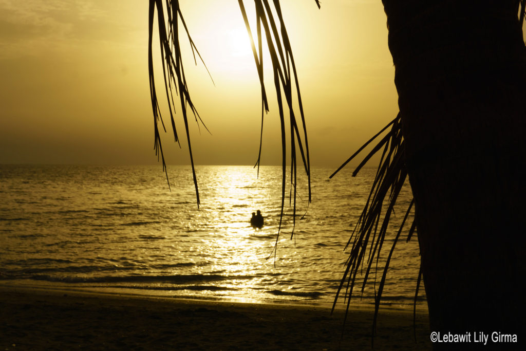 Two people swimming in sea at sunset in Monte Cristi.