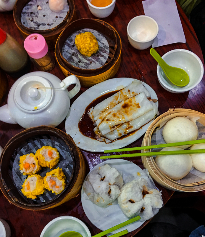 A photo of a birds eye view of dim sum dishes, including siu mai and cheong fun.