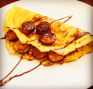 Easy crepes with caramelized banana and chocolate sauce served on a white plate.