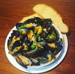 Plump succulent mussels served in a white bowl with a garlic white wine sauce. Sprinkled with parsley and served with a crusty soft white bread.