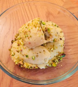 Creamy pistachio ice cream in a glass bowl with chopped pistachios sprinkled on top.