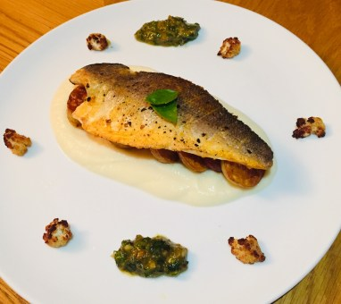 Crispy sea bass fillet on a bed fried potatoes and silky cauliflower puree. Surrounded on the white plate with roasted cauliflower florets and basil pesto.