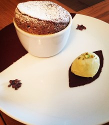 Chocolate Soufflé with Pistachio Ice cream on a white plate