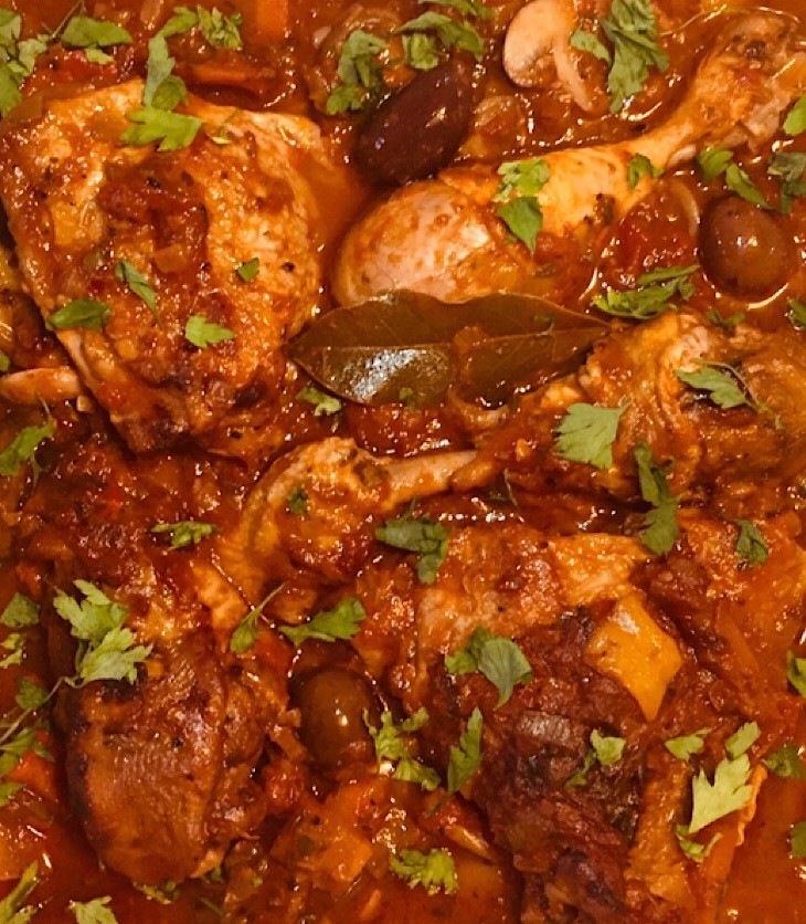 Chicken Cacciatore served in an oven dish. Sprinkled with chopped parsley