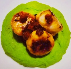 Three scallops on top of black pudding and pea puree on a white plate