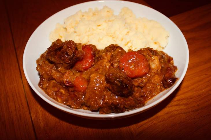Beef and Guinness Stew served in a white bowl with creamy mashed potato.