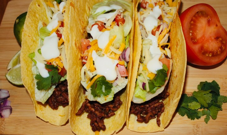 Easy beef taco recipe, tacos topped with crispy lettuce, tomatoes, onions, cilantro, cheese and sour cream. Serve on a wooden board.