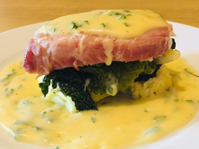 Traditional Irish Bacon and Cabbage sitting on a bed of crushed boiled potatoes. Drizzled with Parsley sauce.