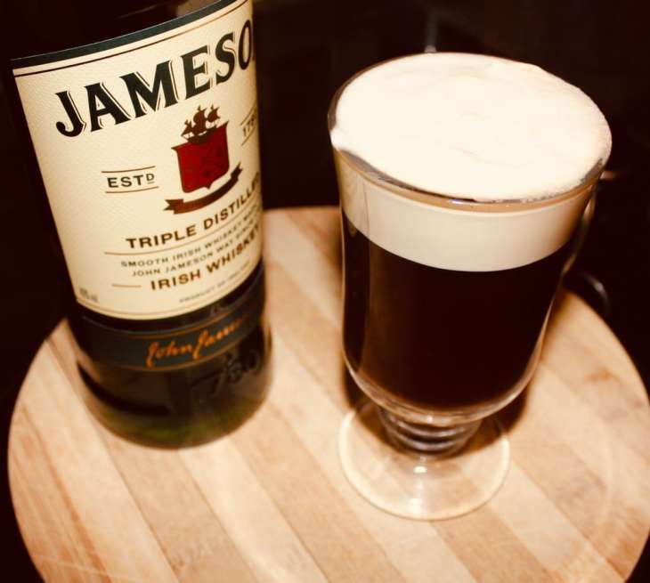 Irish Coffee perfectly made with a bottle of Jameson whiskey beside it.