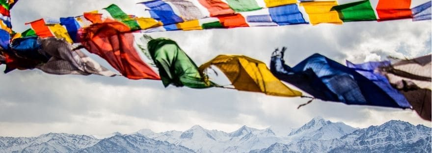 Flags flying across a background of mountains and blue sky
