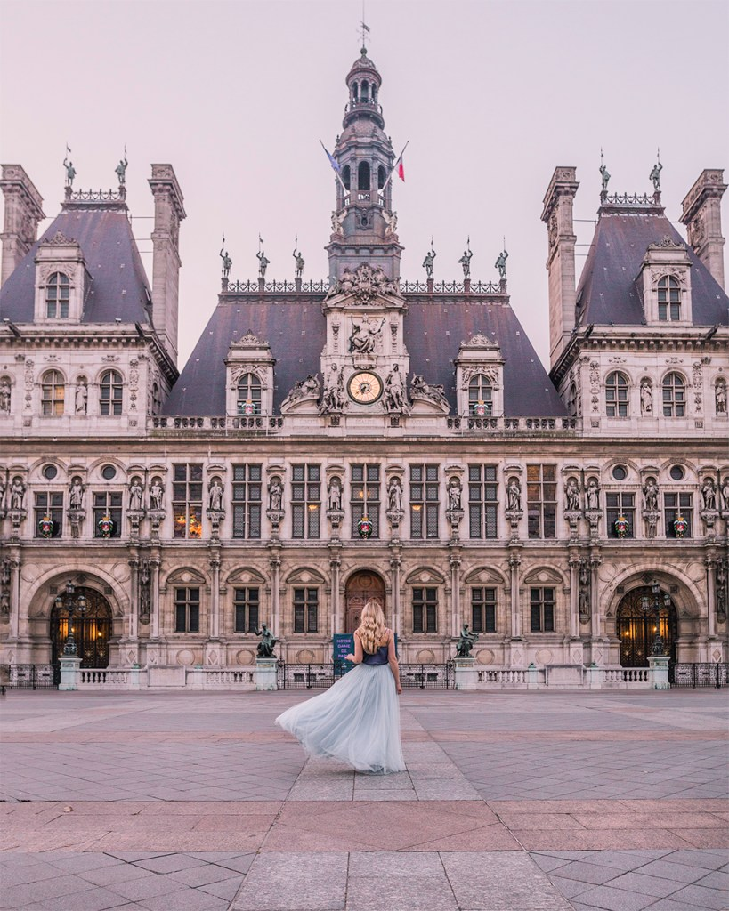 Woman standing in front of the Hotel de Ville of Paris